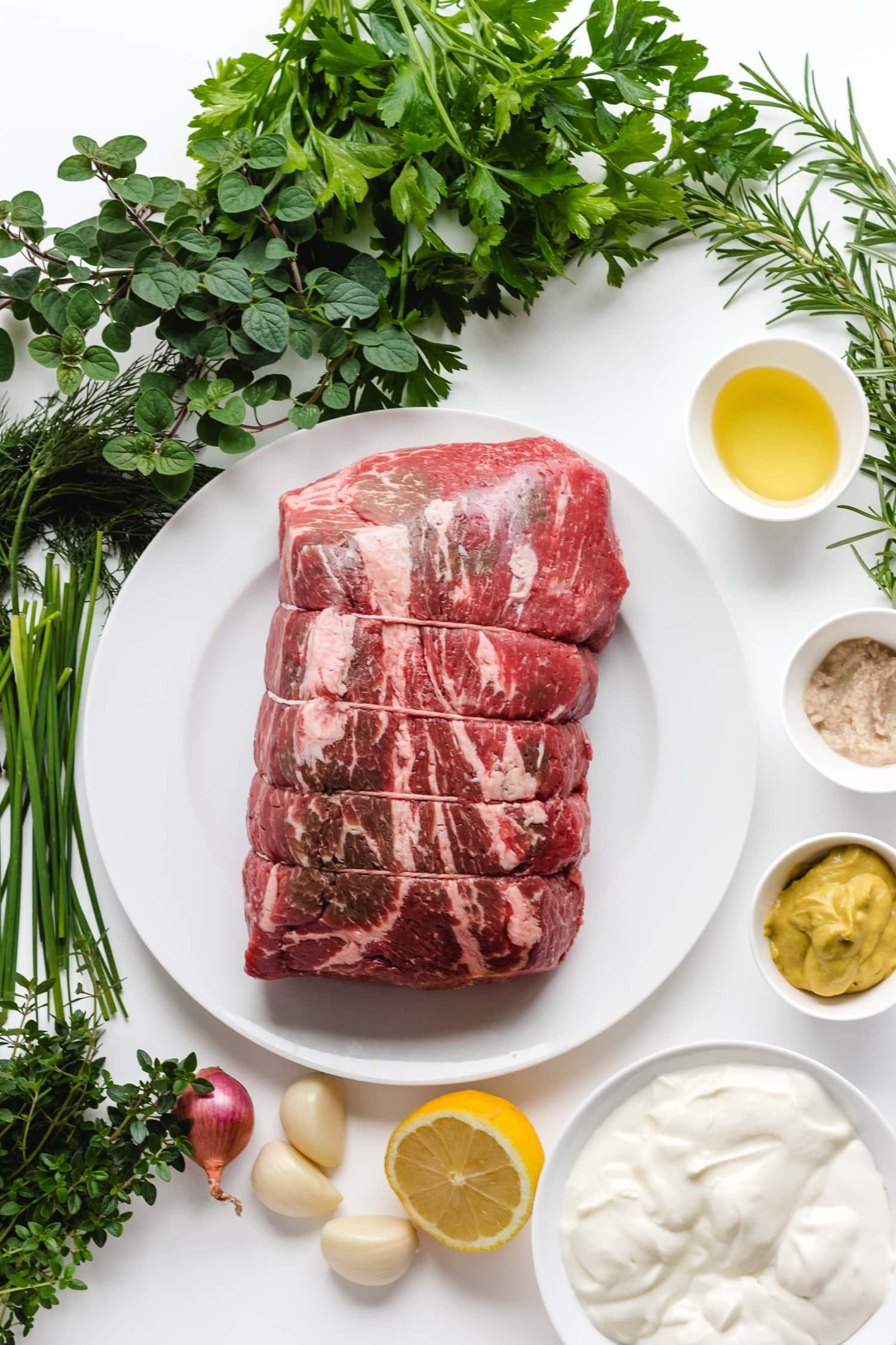 Overhead photo on a white background of all the ingredients needed to make Herb Mustard Crusted Roast Beef with Creamy Herb Sauce.