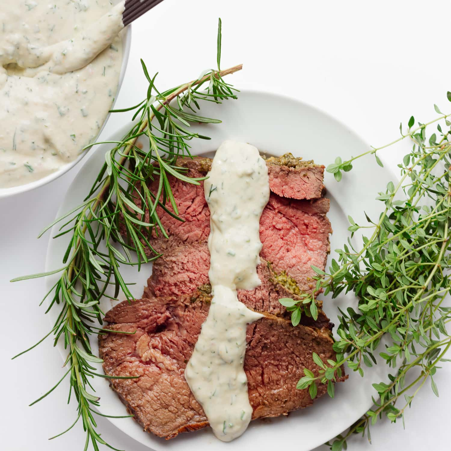 Slices of roast beef on a white plate with a drizzle of creamy herb sauce down the middle.  There is also a bowl of the same sauce in the corner and a sprig of rosemary and thyme on each side of the plate.