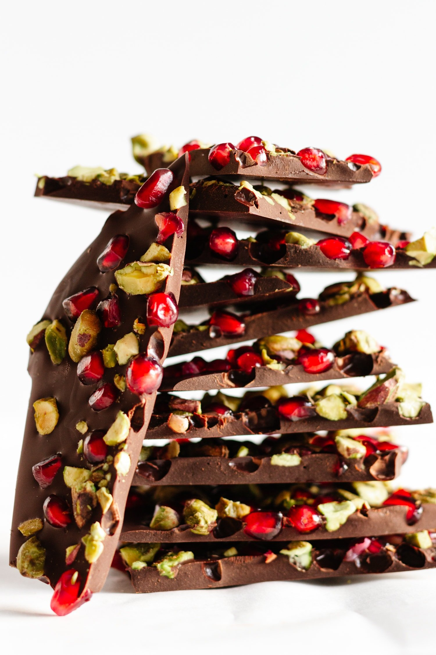 Piled up pieces of Pomegranate + Pistachio Dark Chocolate Bark on a white background.
