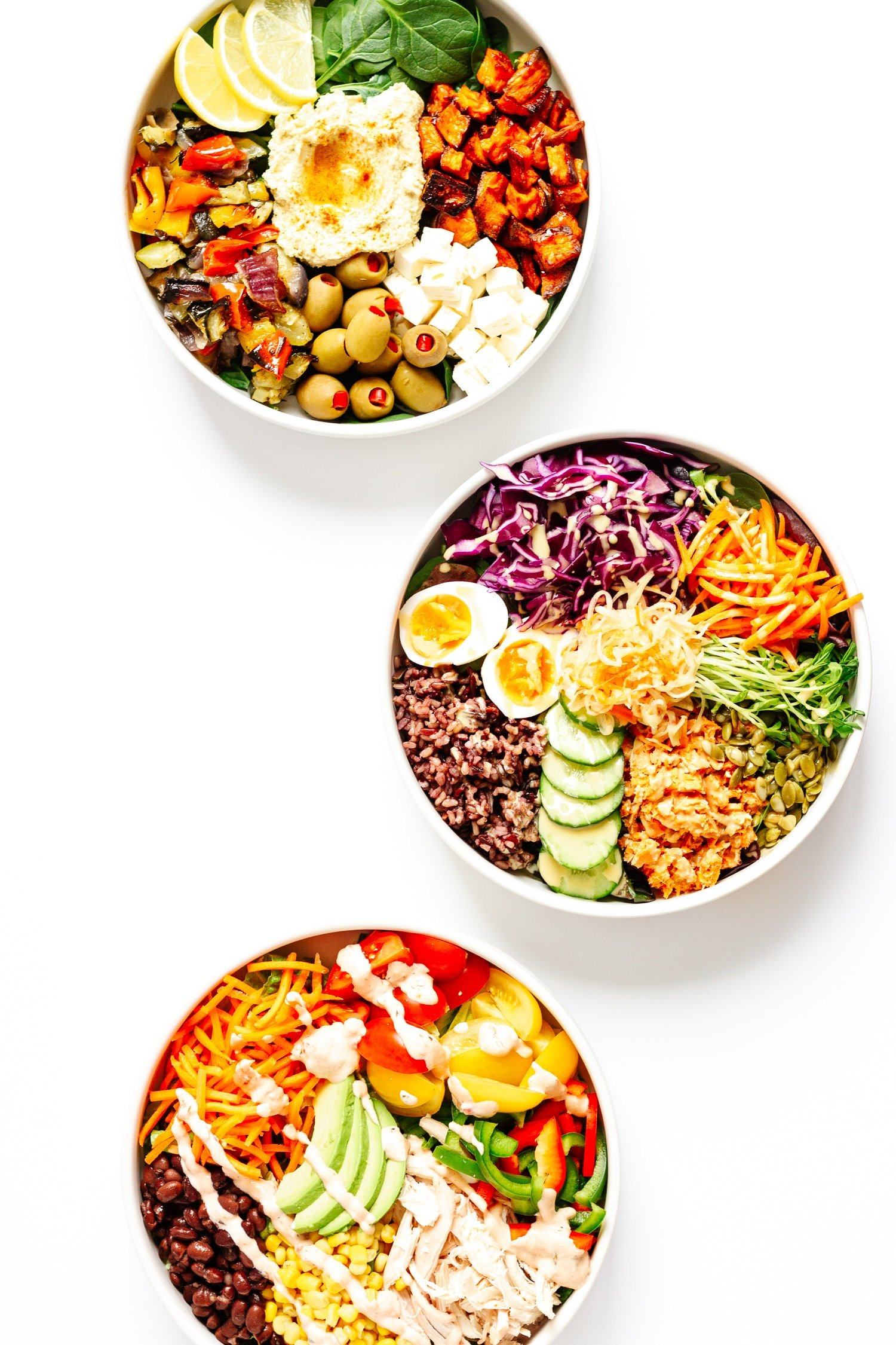 Three different healthy nourish bowls arranged in a curve on a white background.