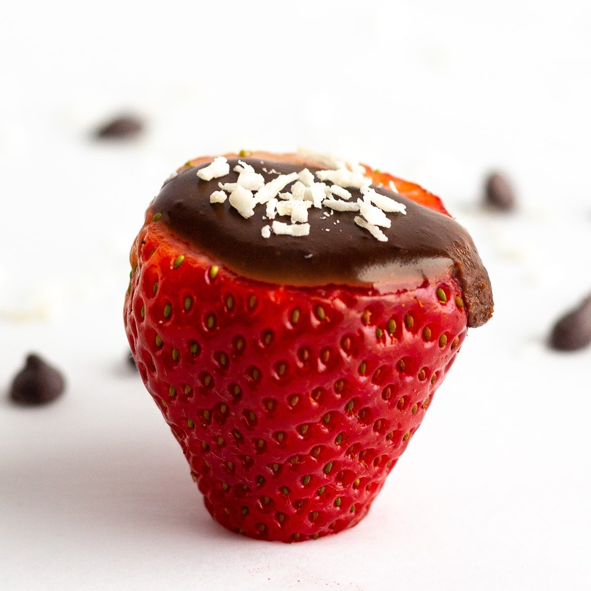 Single strawberry filled with chocolate coconut cream and a few flakes of shredded coconut scattered on the top.