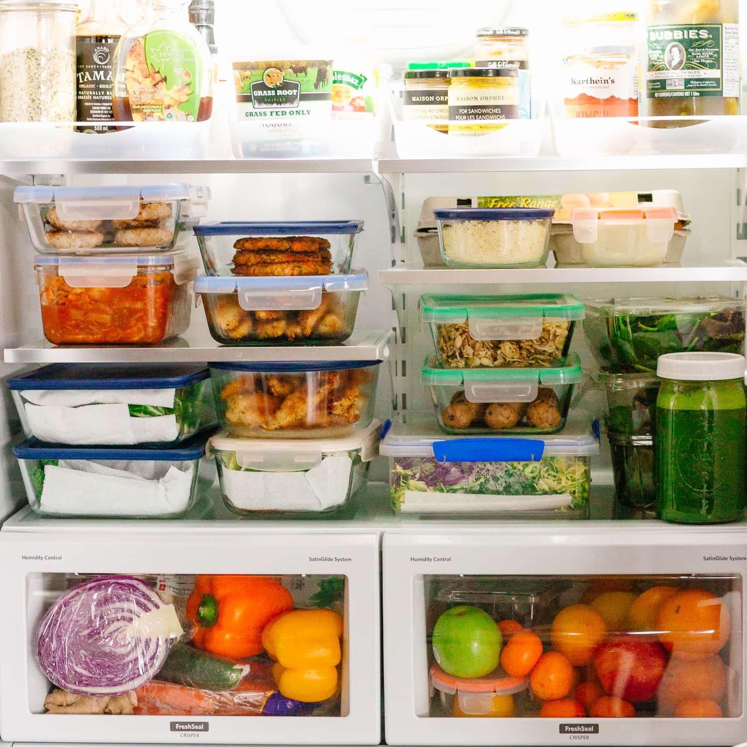 Inside of a fridge filled with containers of meal prep recipes made from The HealthNut Cookbook