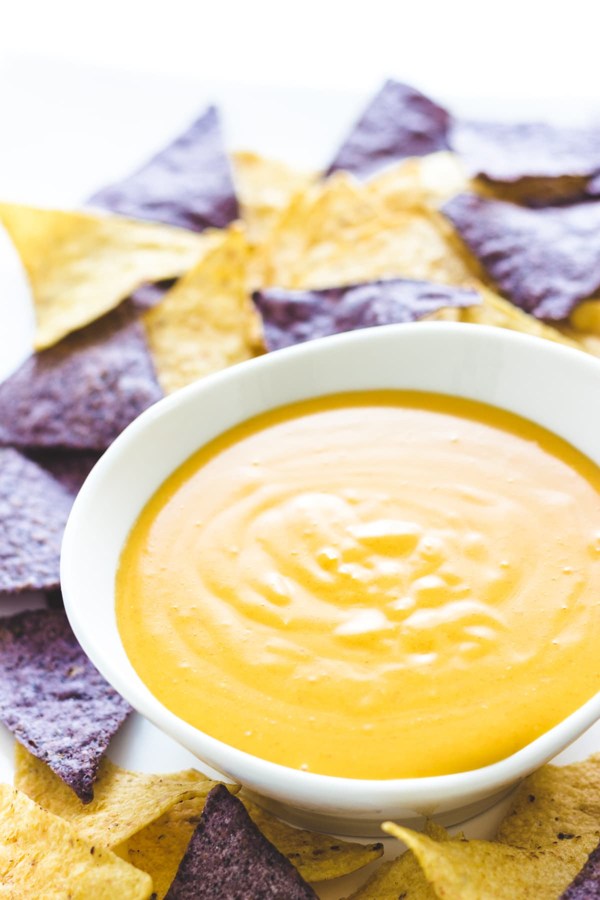 Homemade nacho cheese sauce in a white bowl surrounded by yellow and blue corn tortilla chips