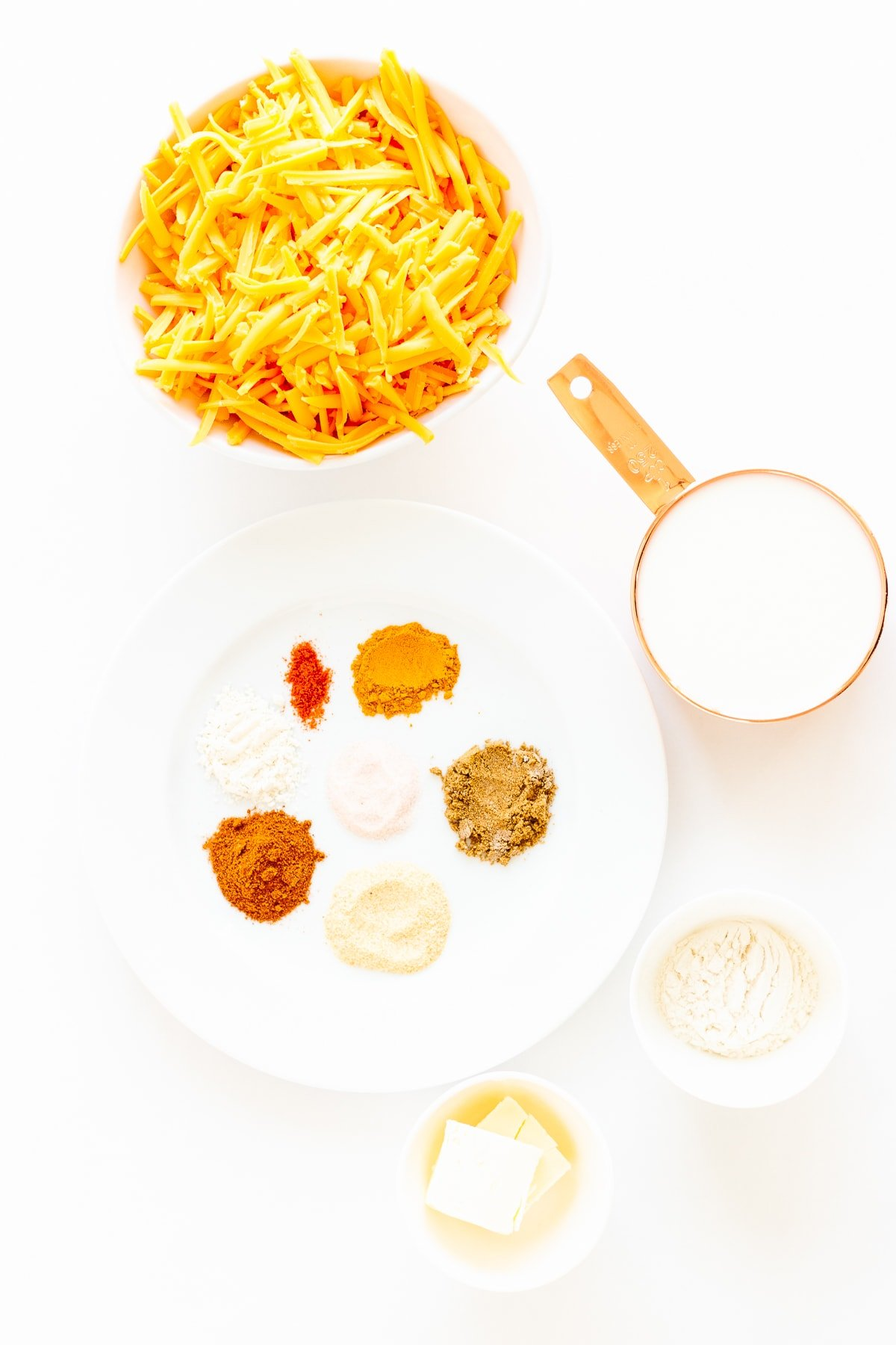 All the ingredients needed to make homemade nacho cheese sauce laid out on a white surface.