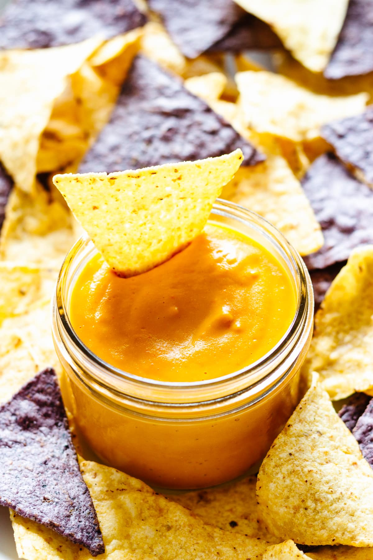 Mason jar filled with vegan nacho cheese sauce and surrounded by yellow and blue corn tortilla chips
