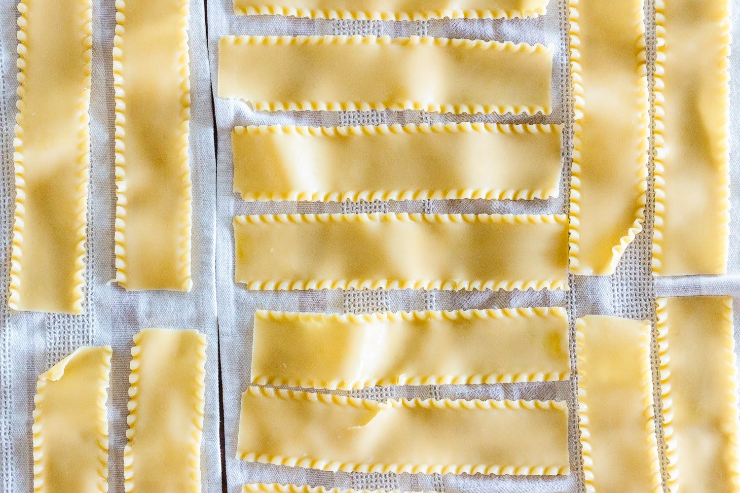 Cooked lasagna noodles laid out on dish towels.