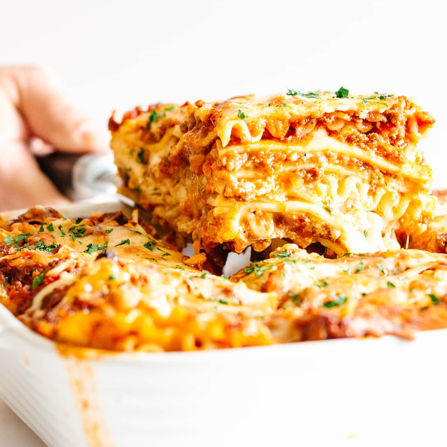 Slice of lasagna being lifted out of casserole dish.