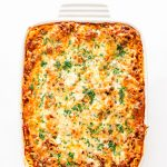 Overhead shot of lasagna in a white dish on a white background