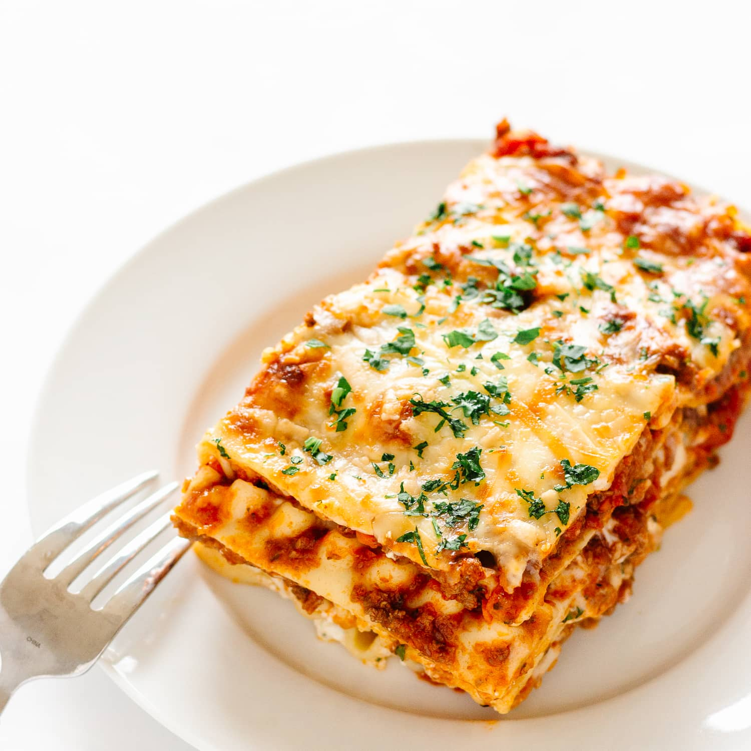 Slice of lasagna on a white plate with fork resting on the side.