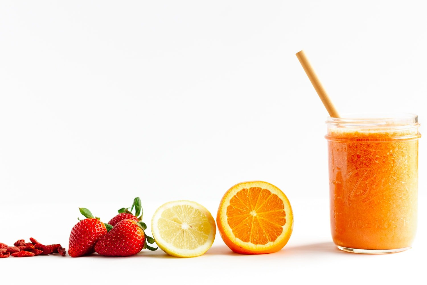 Goji berries, strawberries, lemon, orange and glass of Vitamin C Smoothie lined up on a white background.
