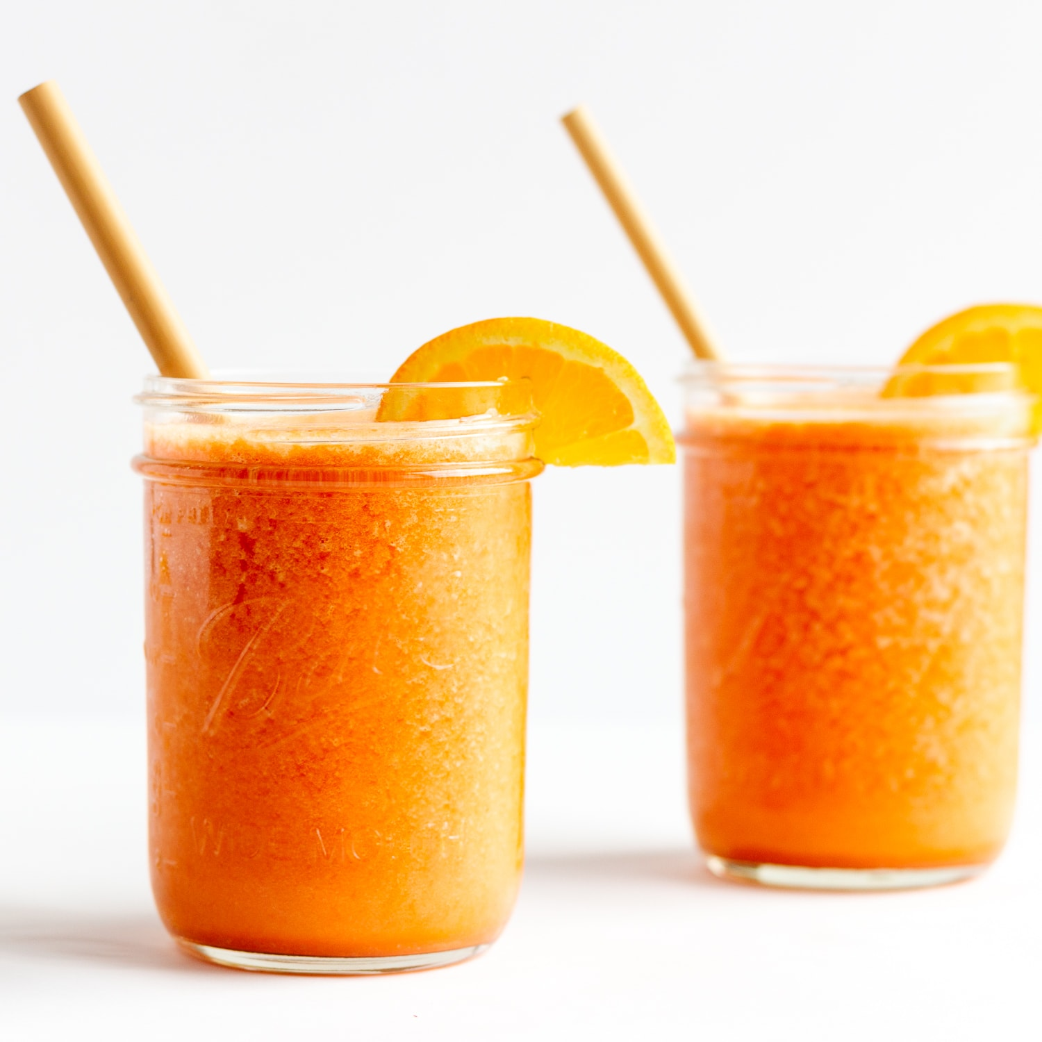 Two mason jars filled with Vitamin C Immune Boosting Smoothie and garnished with orange slices and a bamboo straw.
