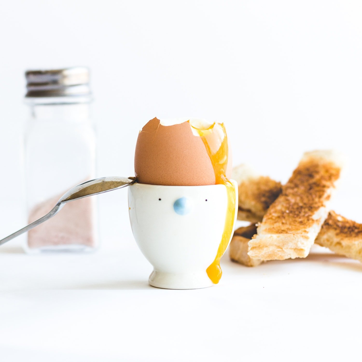 Soft boiled egg in egg cup with top off, yolk running down the side and spoon leaning on the edge.  Pile of toast soldiers and salt shaker in the background.