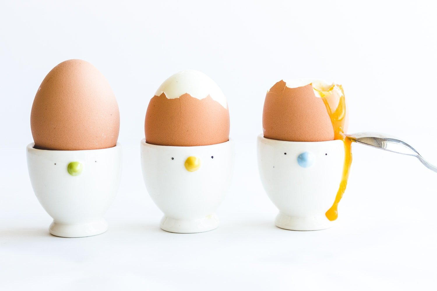Three soft boiled eggs in egg cups with yolk running down the side of the last one and a spoon resting against it