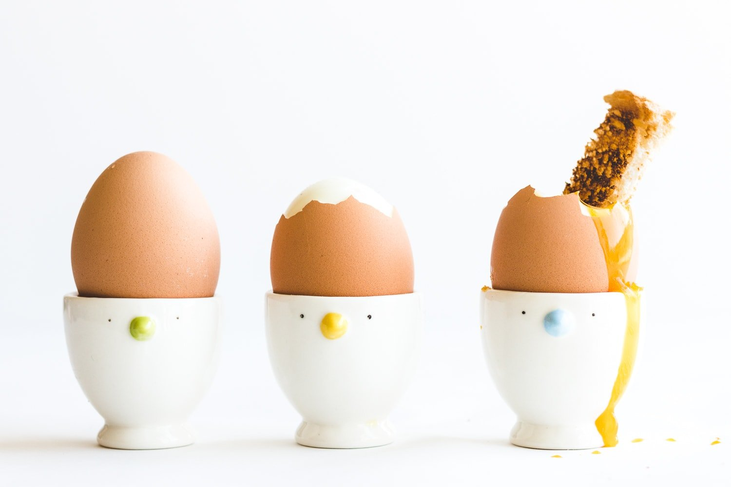 Three soft boiled eggs in egg cups.