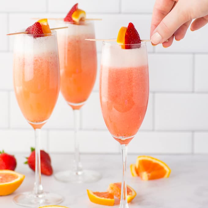 Three champagne flutes filled with strawberry mimosa and garnished with sliced orange and strawberry.