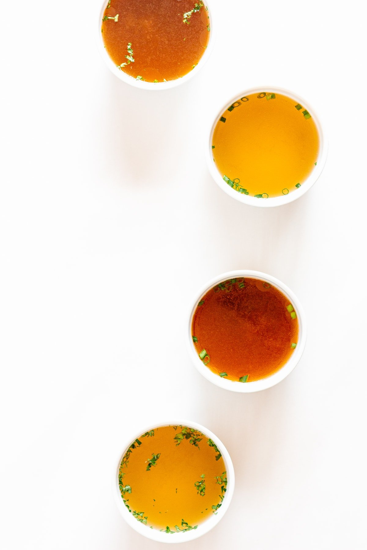 Overhead shot of four small white bowls of broth arranged in a curved shape on a white background.