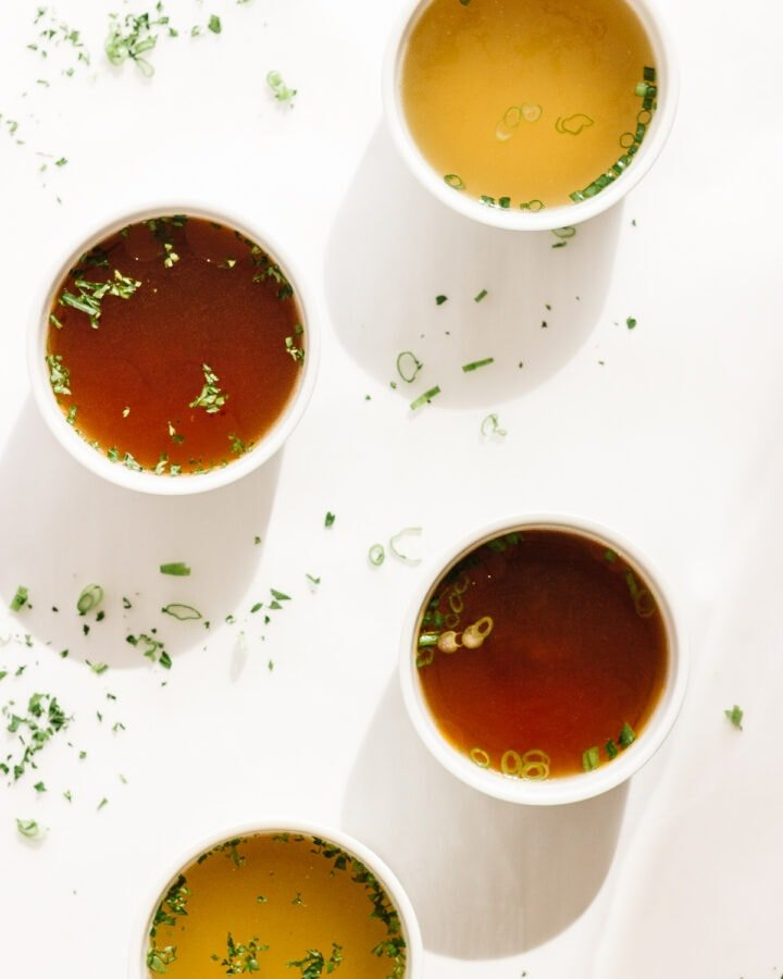 Four white bowls of broth on a white background with scattered chopped herbs.