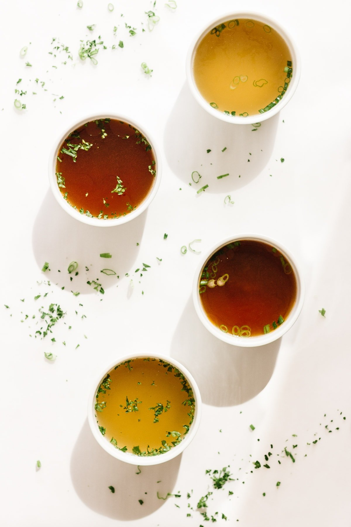 Four white bowls of broth set on a white background with chopped herbs scattered.