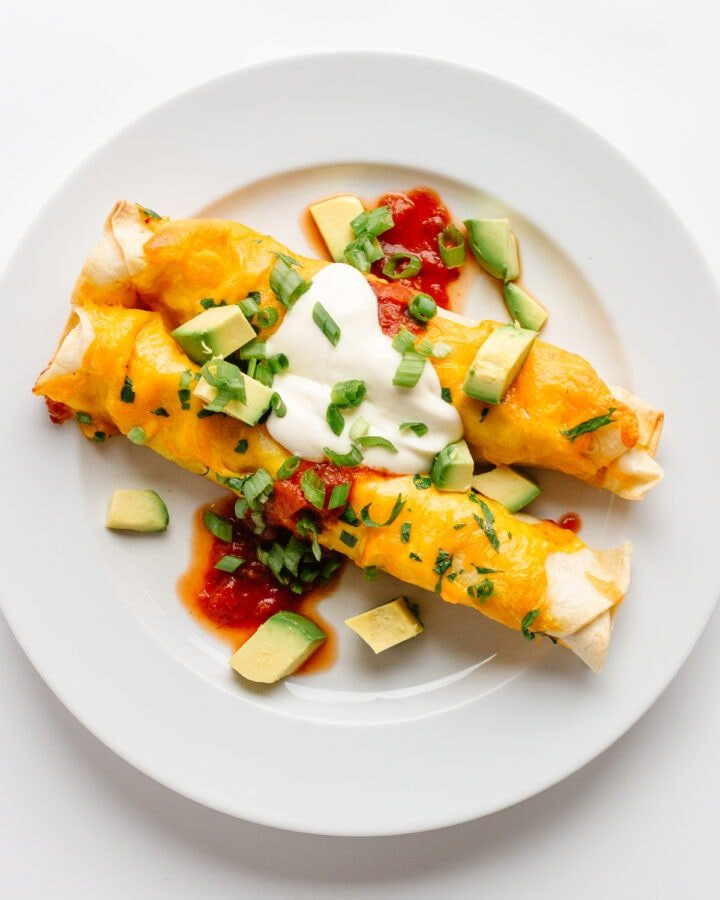 Two cheesy chicken enchiladas on a white plate and garnished with salsa, sour cream, cubed avocado and chopped green onion.