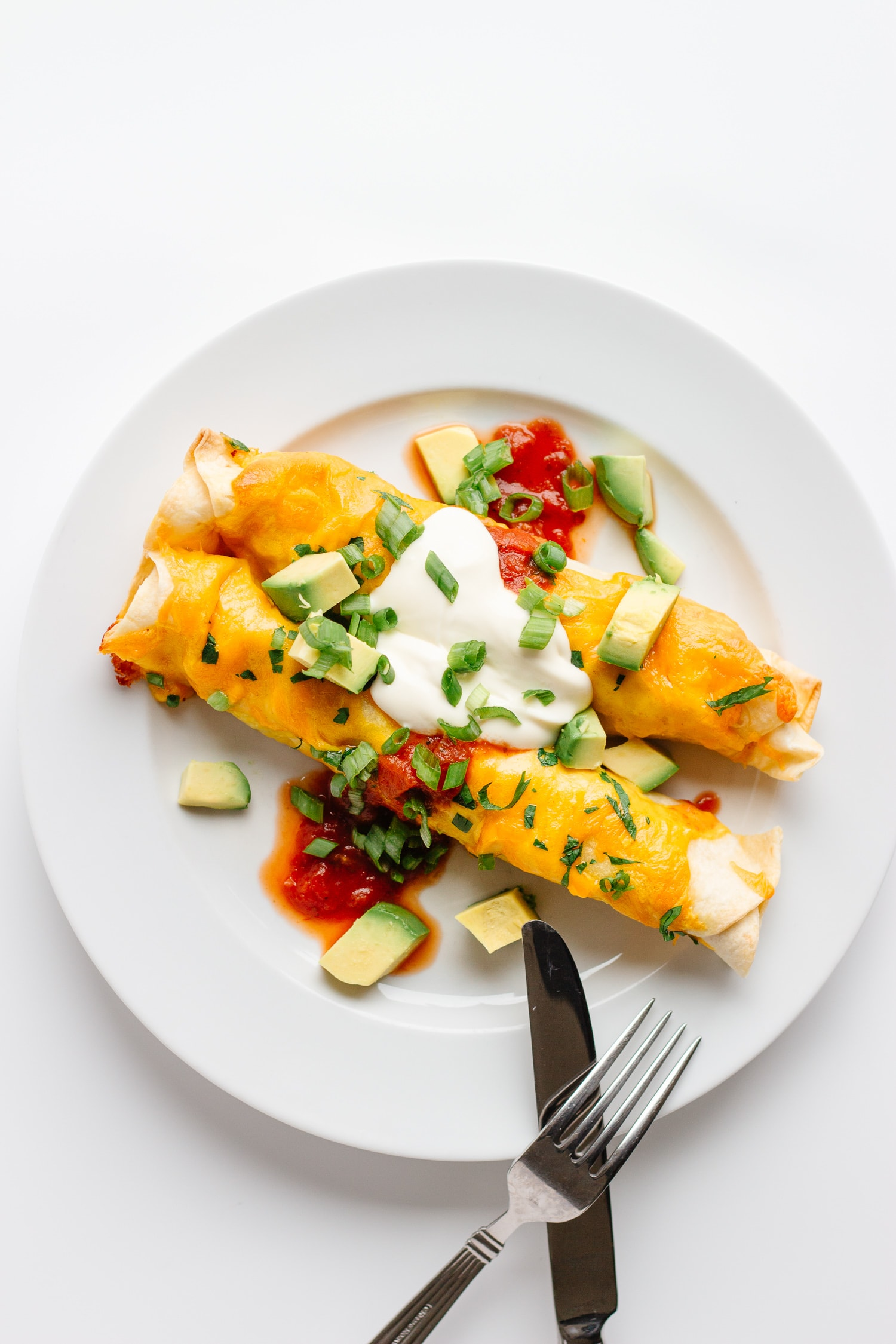 Two cheesy chicken enchiladas on a white plate garnished with cubed avocado, salsa, sour cream and chopped green onions.