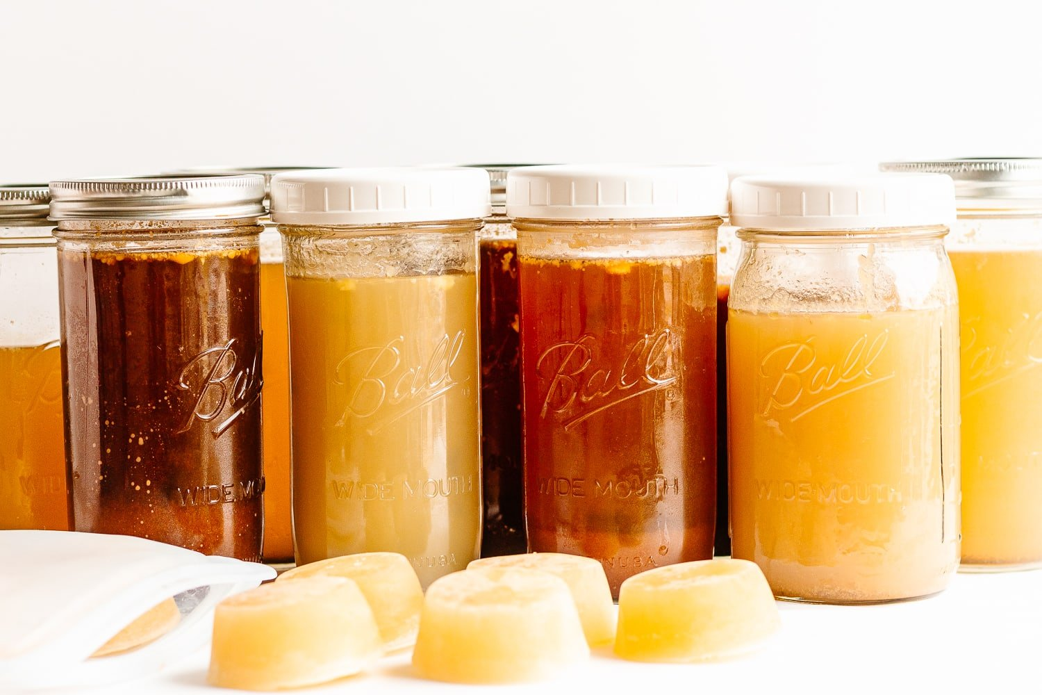 "A variety of mason jars filled with broths and stocks with some frozen broth ""pucks"" in front."