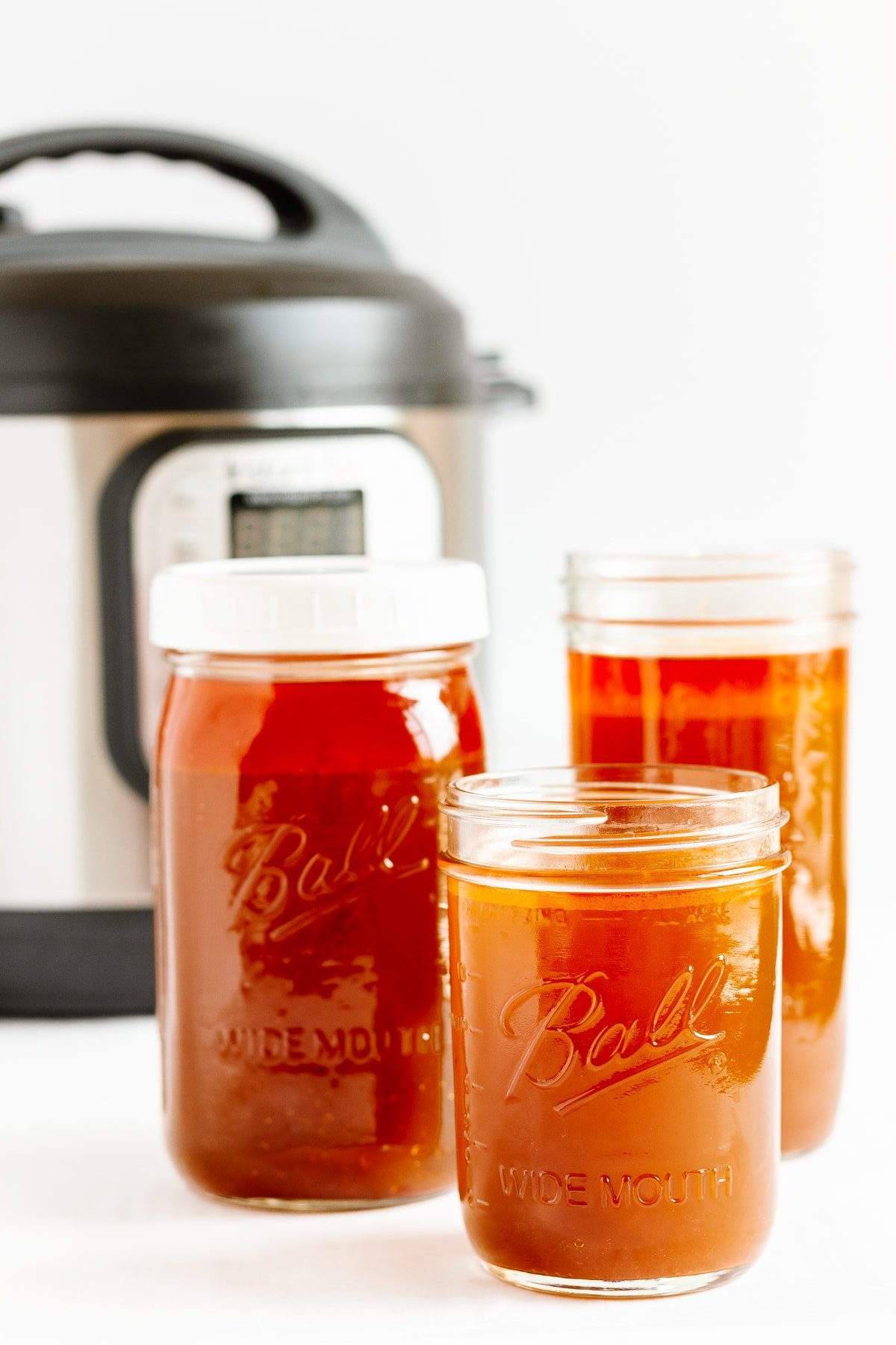 Three mason jars of beef bone broth with Instant Pot in the background.