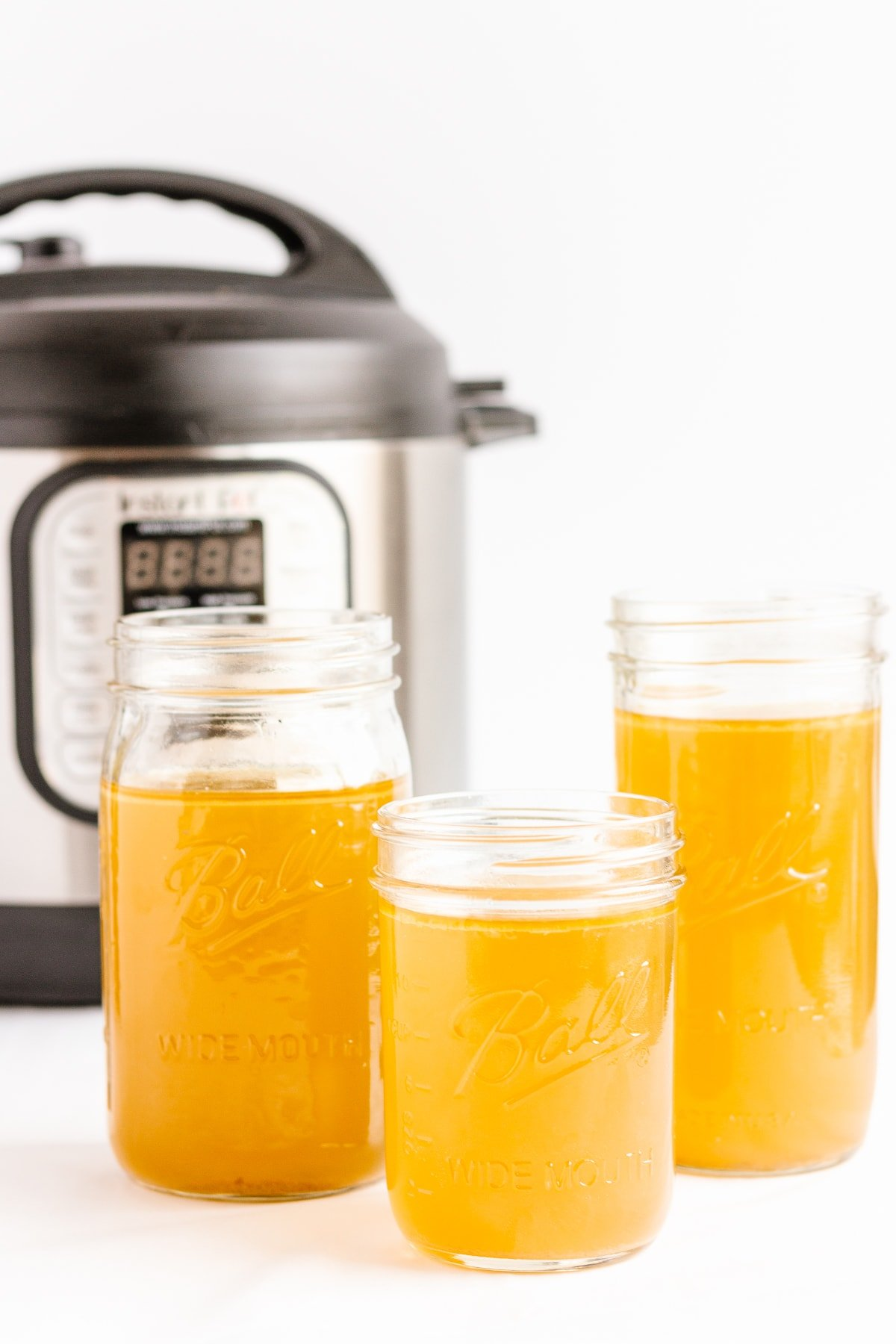 Three jars of chicken bone broth standing in front of an Instant Pot.