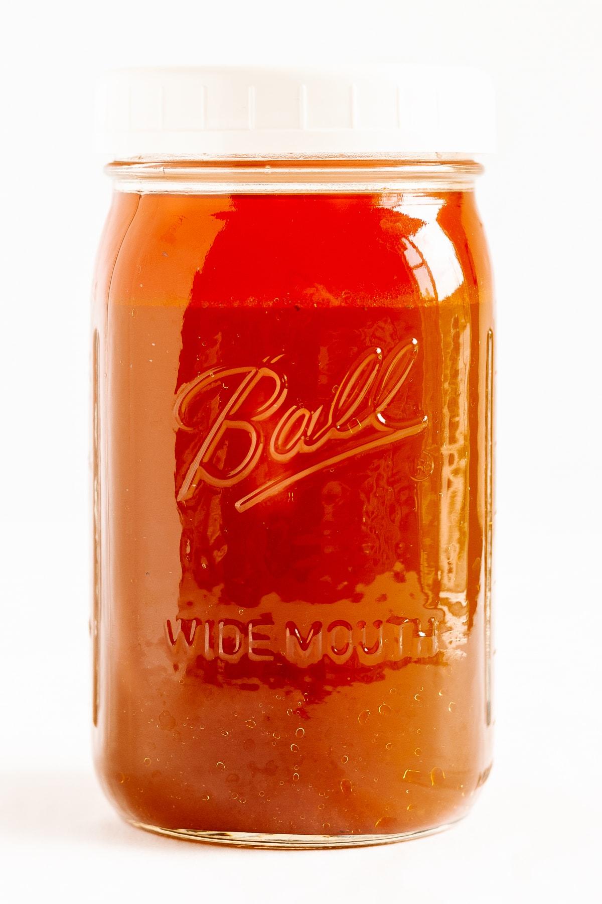 Mason jar of beef bone broth (stock) on a white background.