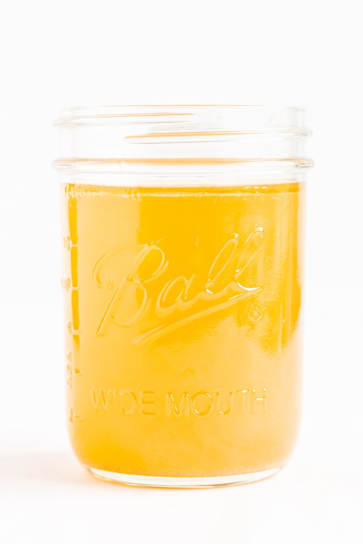 Mason jar filled with chicken bone broth on a white background.