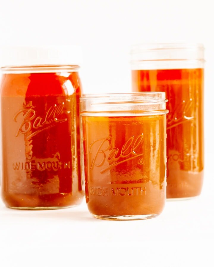 Three different sizes of mason jars filled with beef bone broth (stock) on a white background.