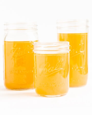 Three mason jars of chicken bone broth (stock) on a white background.