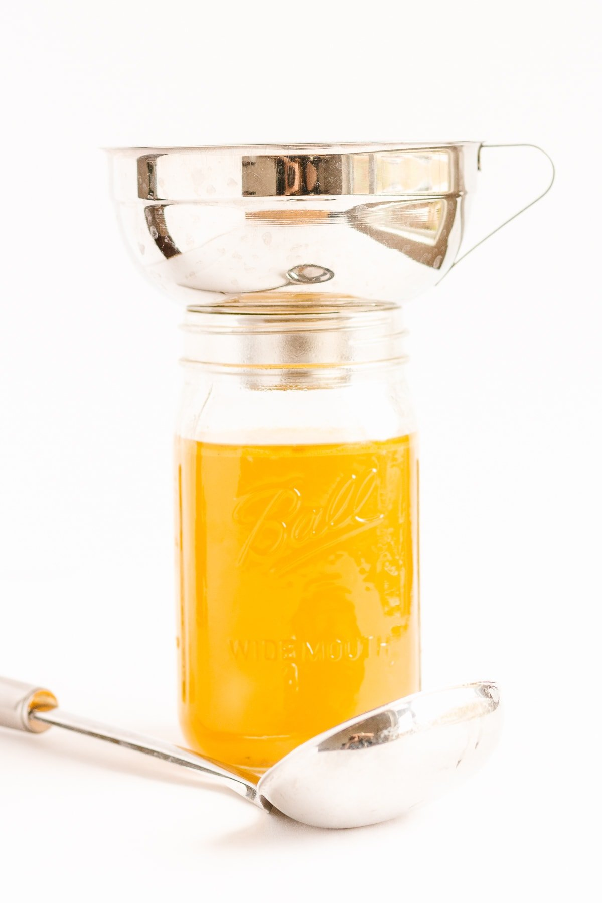 Wide mouth funnel set on top of mason jar filled with broth and ladle lying in front.