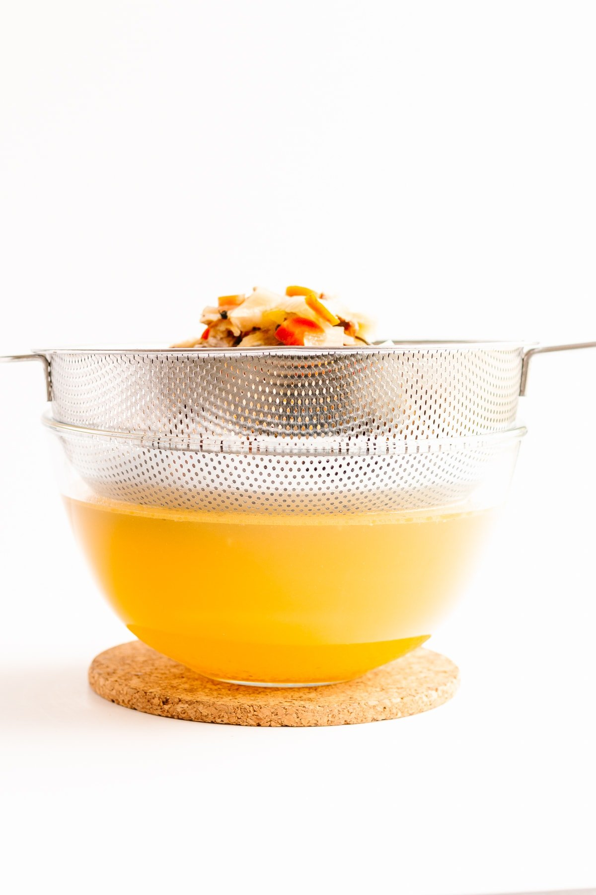 Fine mesh sieve positioned over clear glass bowl straining chicken broth.