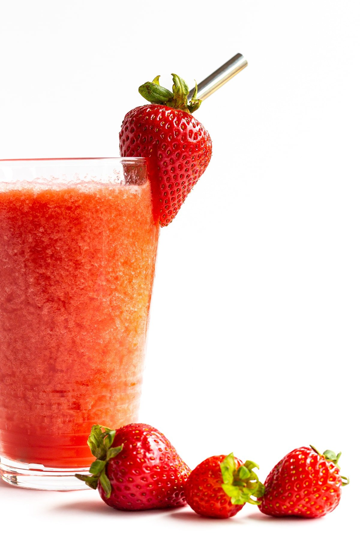 Glass of strawberry slushie with fresh strawberries scattered next to it.