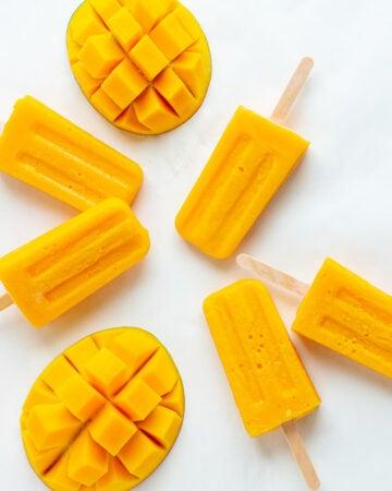 Overhead photo of mango popsicles and fresh mango halves on a white background.