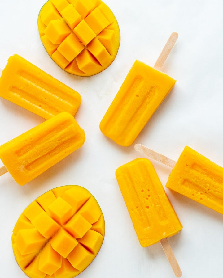 Overhead photo of mango popsicles and fresh mango halves on a white background.