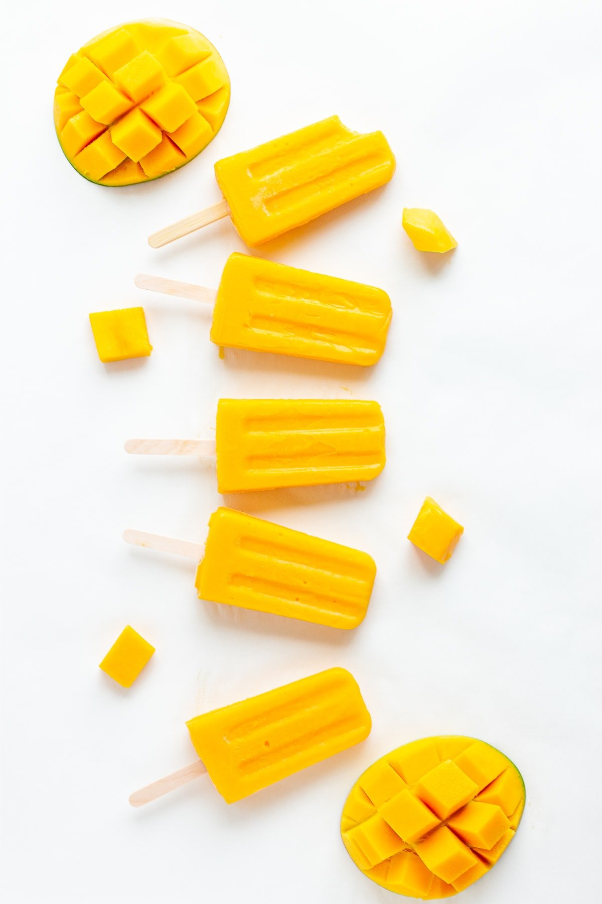 Mango popsicles and fresh mango displayed on a white background.