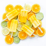 Overhead shot of five orange coloured popsicles displayed on top of orange, lemon and lime slices.
