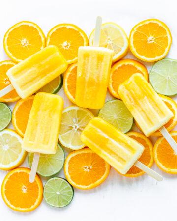 Overhead shot of five orange coloured popsicles displayed on top of orange, lemon and lime slices.