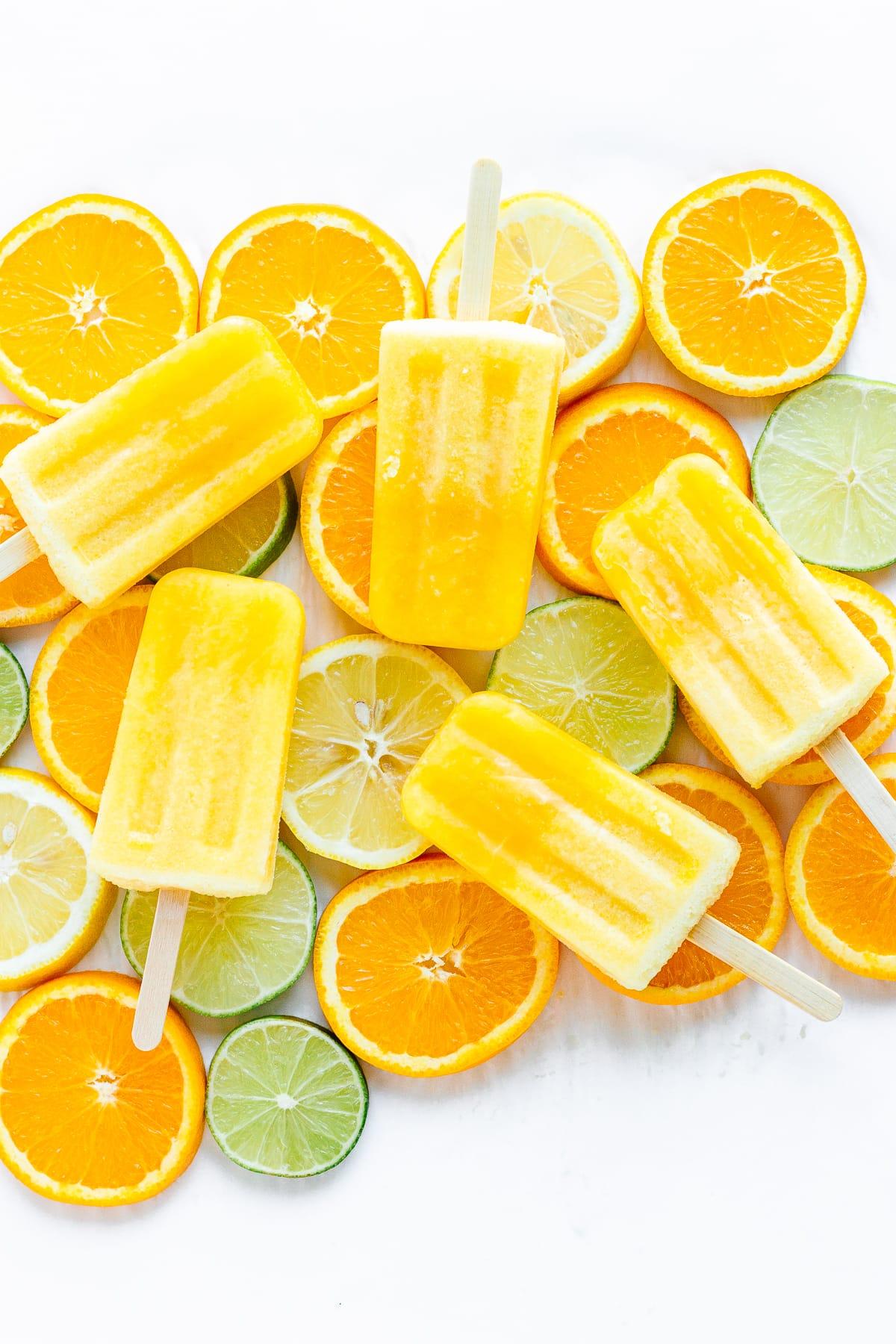 Five orange lemon lime popsicles displayed on top of a variety of sliced citrus.