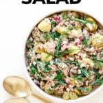 "Bowl of salad with gold salad servers and text overlay that reads ""Tuna Potato Salad""."