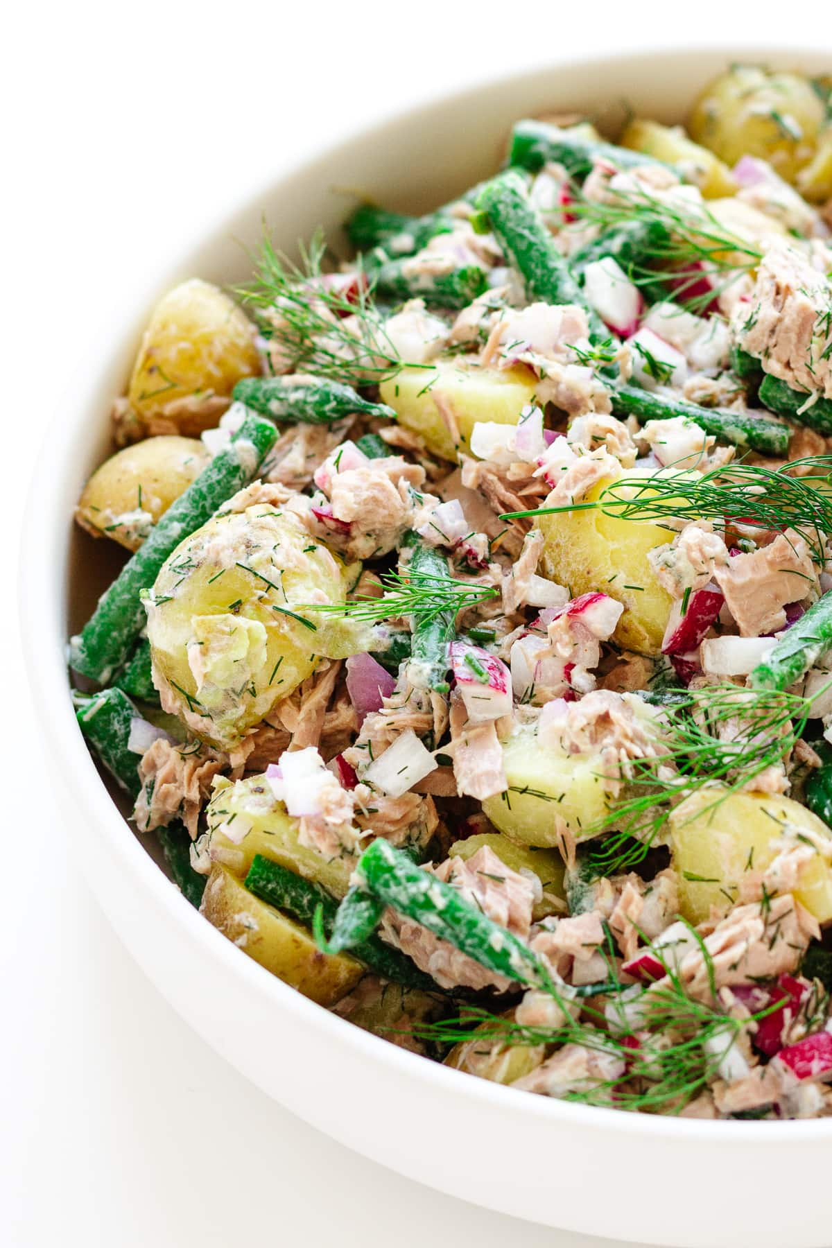 Close up photo of tuna potato salad in white bowl.