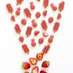 Variety of strawberry gummies in different shapes and a couple fresh strawberries on a white background.