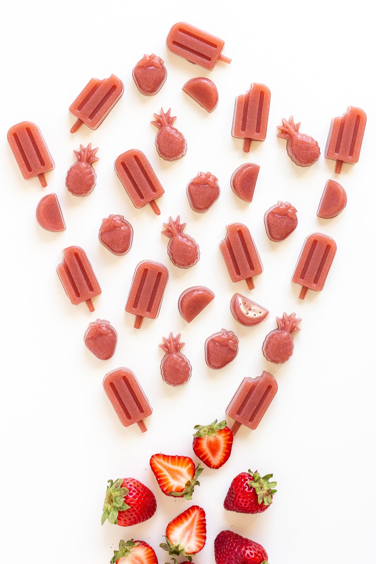 Variety of different shaped homemade gummies and fresh strawberries on a white background.