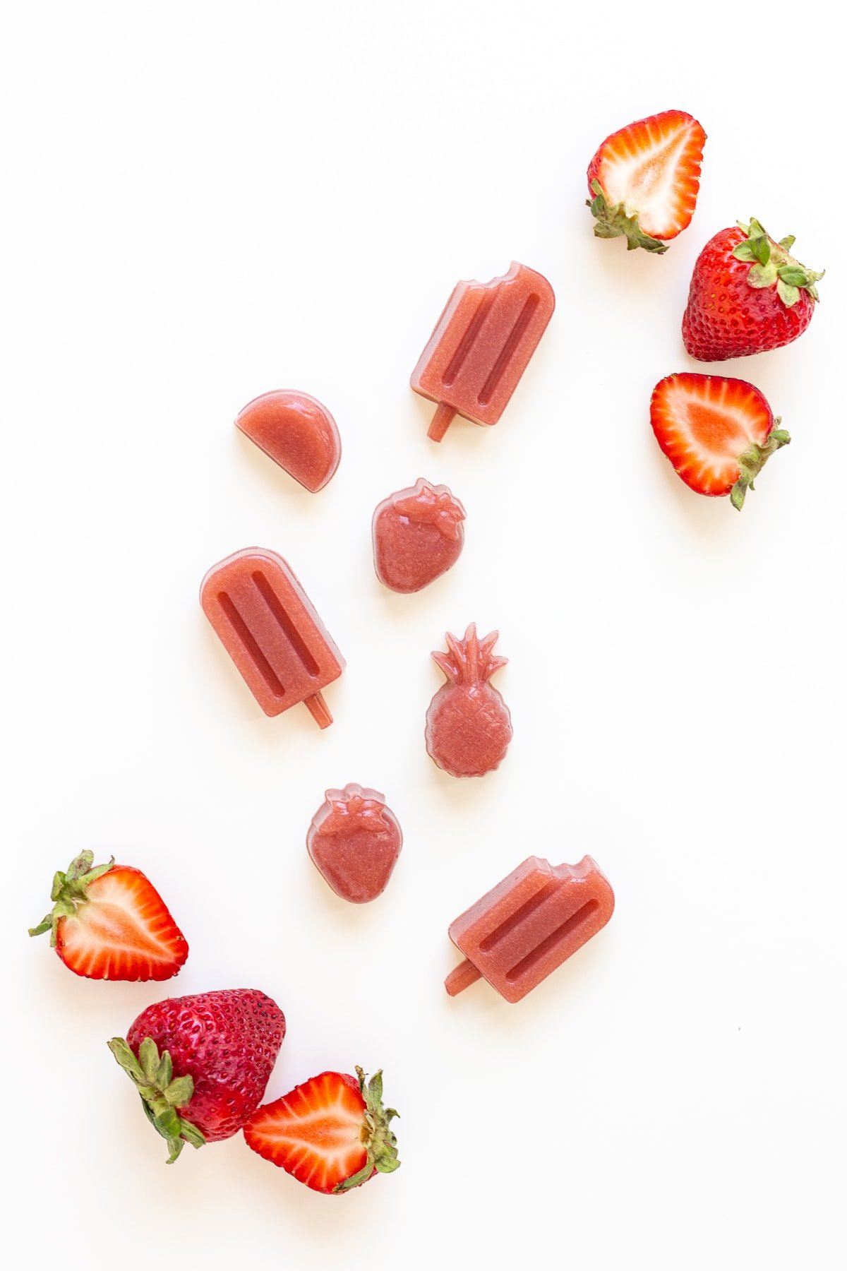 Strawberry gummies and fresh strawberries on a white background.