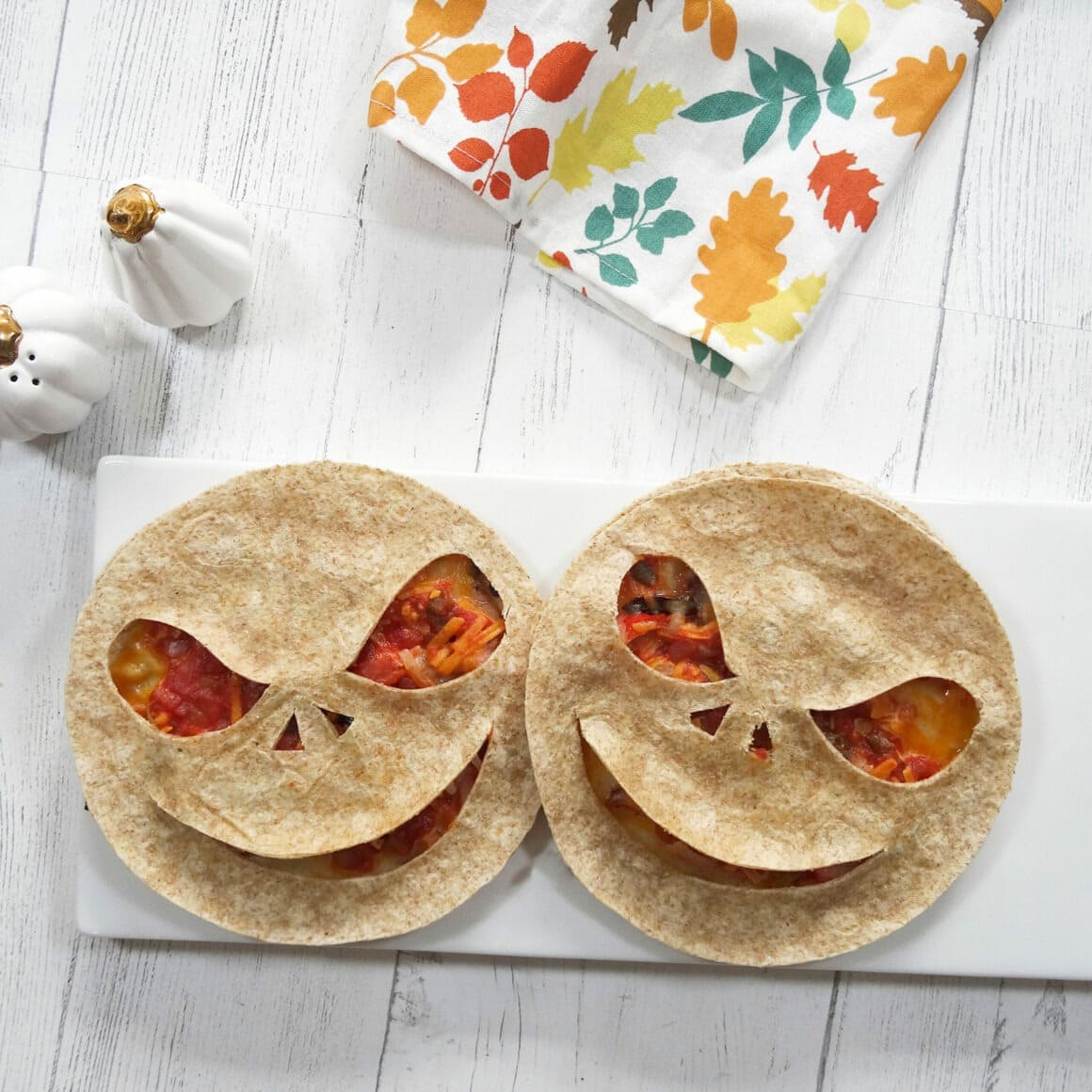 Two quesadillas with creepy faces carved into them for Halloween.