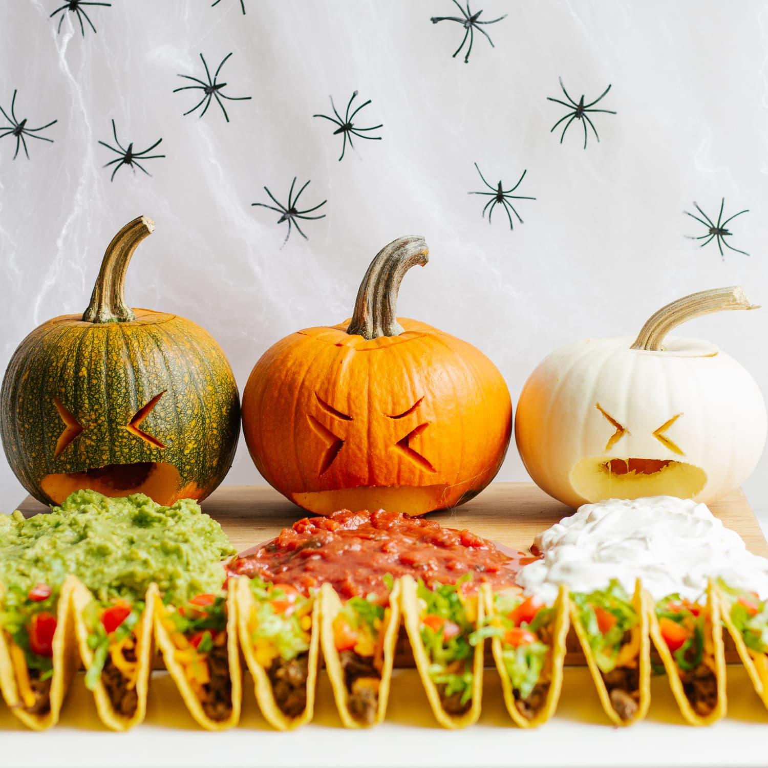 Halloween themed taco board with three pumpkins puking guacamole, salsa and sour cream.