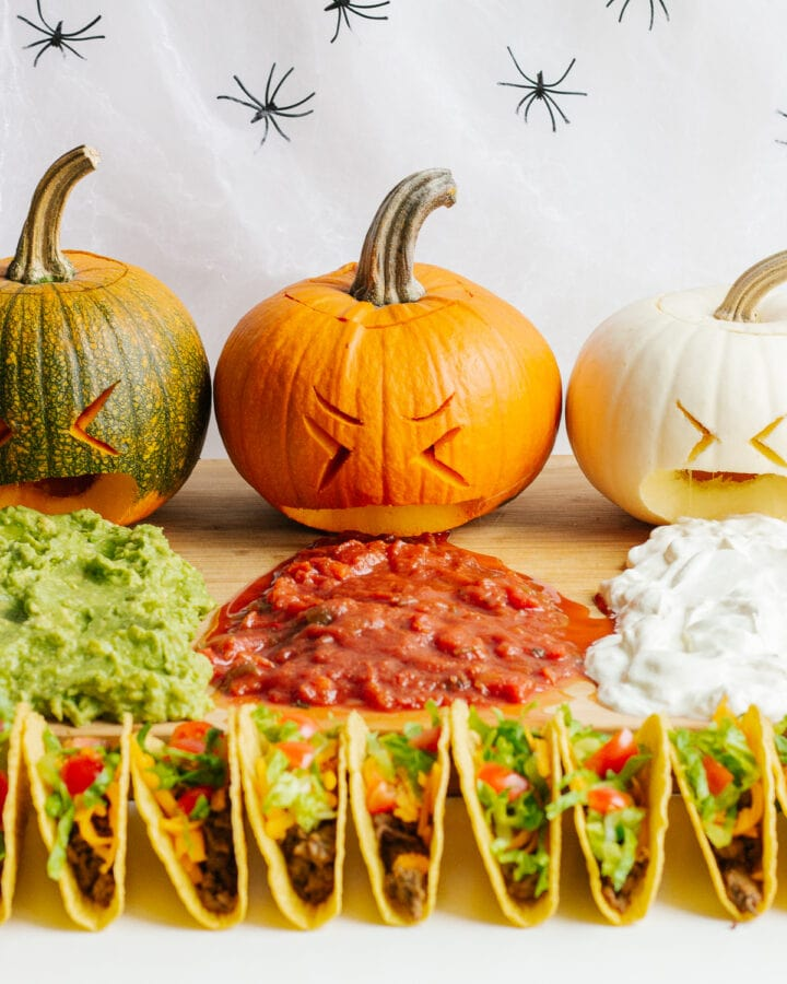 "A Halloween themed taco board featuring three carved pumpkins ""puking"" guacamole, salsa and sour cream."