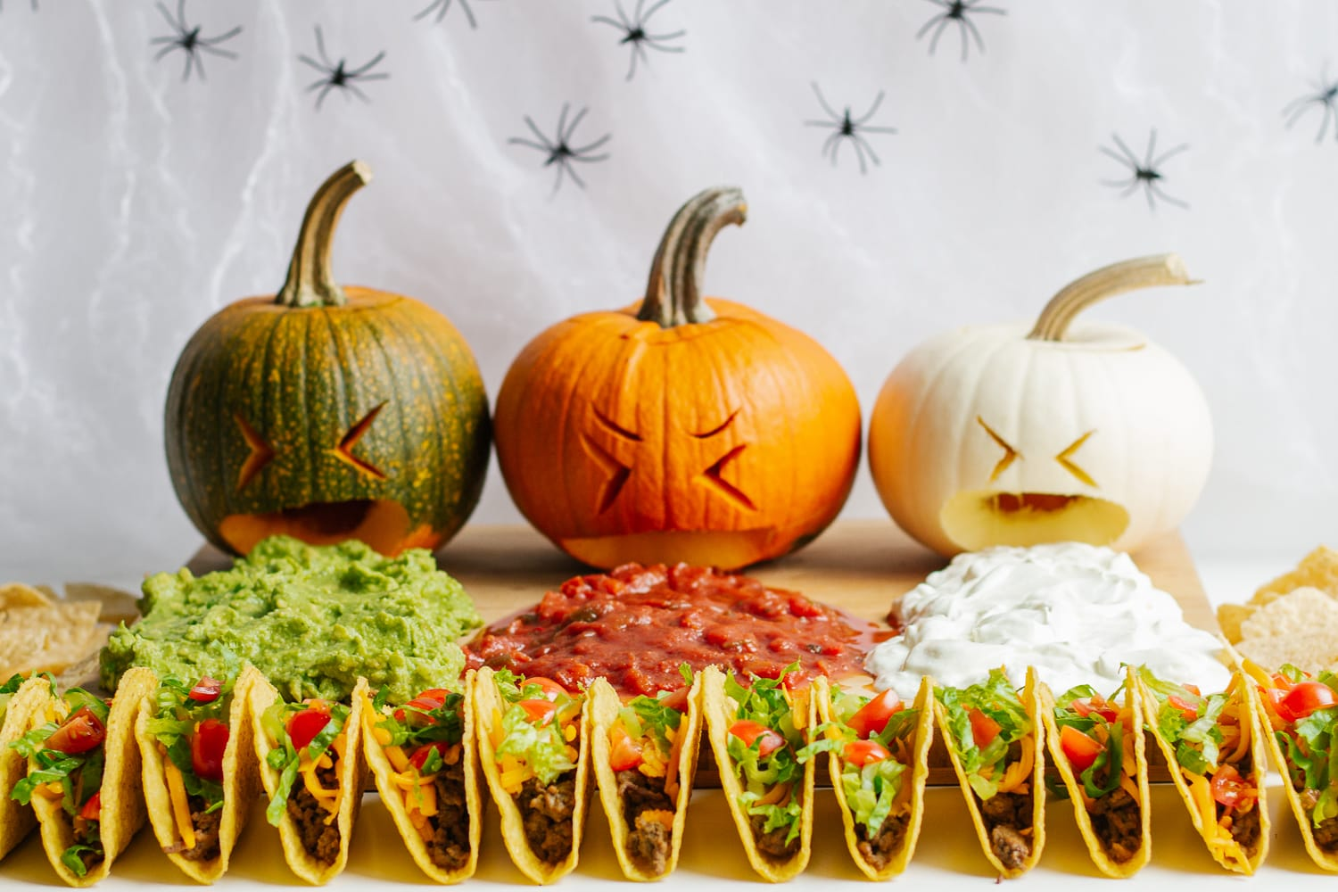 A Halloween taco board featuring three topping puking pumpkins.