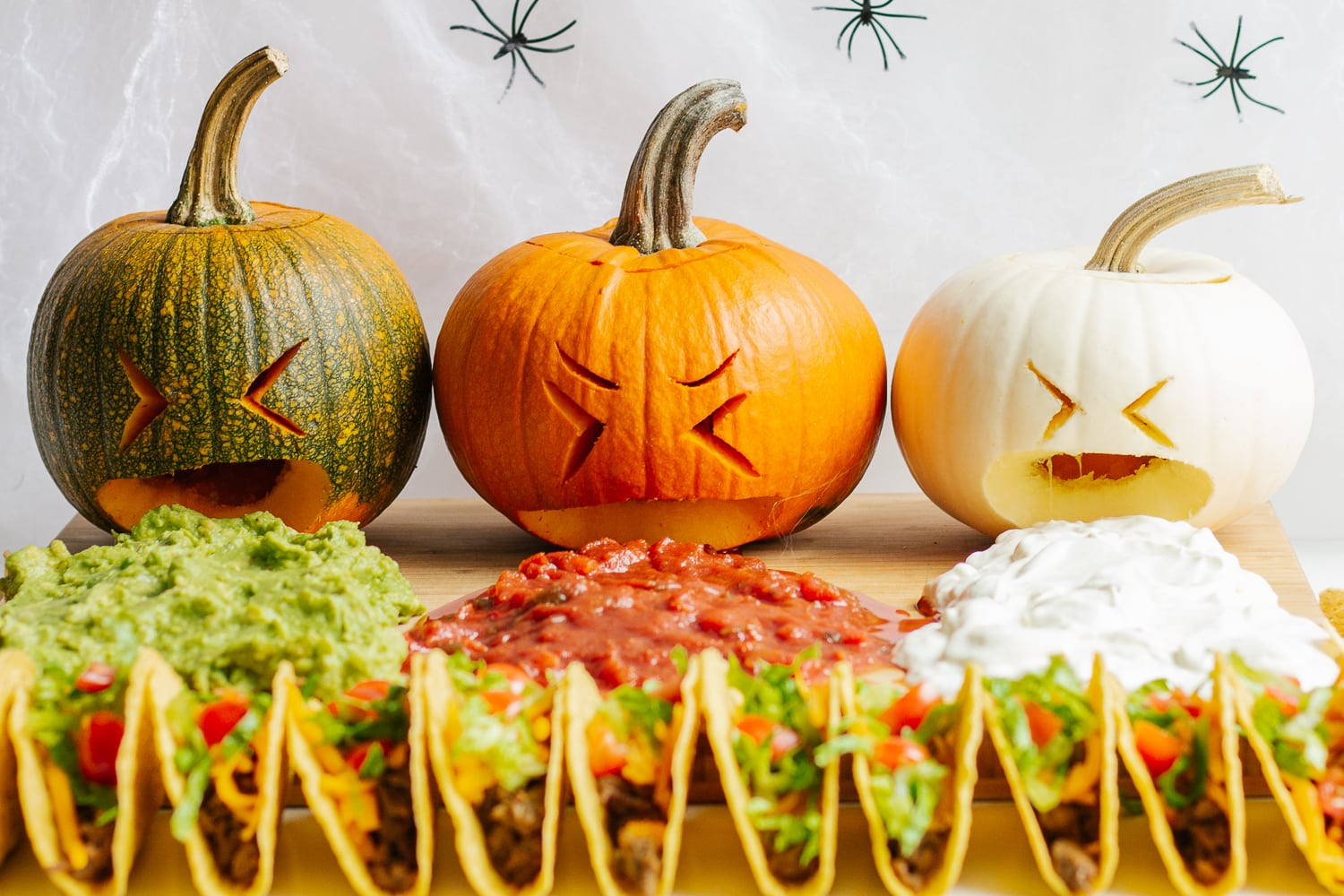 A taco board with a trio of puking pumpkins.